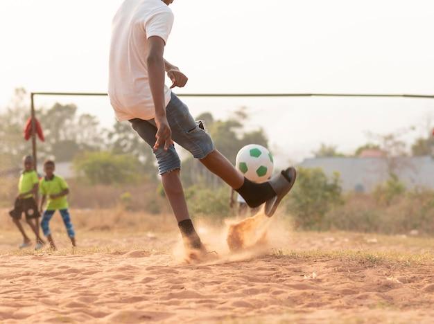Sluit omhoog jongen die achter bal loopt