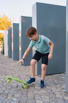 Sluit omhoog jongen die blauwe tennisschoenen dragen oefenend met groen skateboard. actieve stedelijke levensstijl van jeugd, opleiding, hobby, activiteit. actieve buitensport voor kinderen. kind skateboarden.