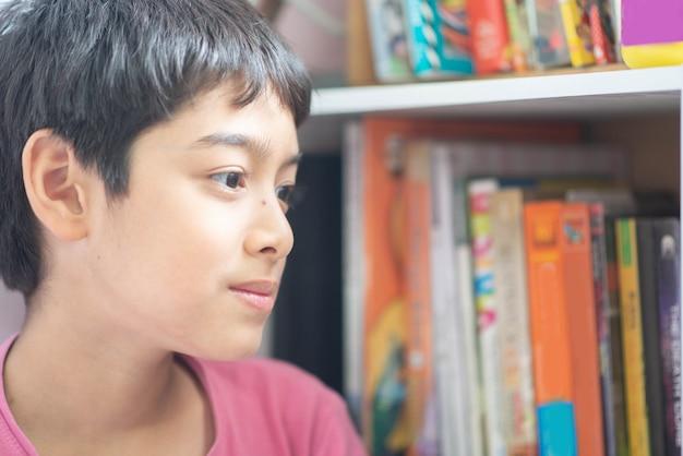 Sluit omhoog jongen in de bibliotheek met hoogtepunt van boeken