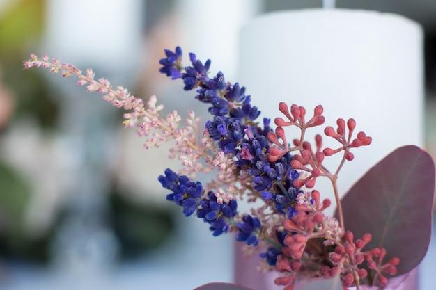 Sluit omhoog kaars met verse eucalyptus, astilbe en lavendeltakken wordt verfraaid verbindend met roze band die.