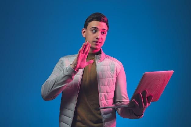 Sluit omhoog kaukasisch man portret dat op blauwe studio in neonlicht wordt geïsoleerd