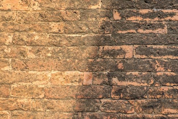 Sluit omhoog klei oranje bakstenen muur in zonsopgang, textuurachtergrond