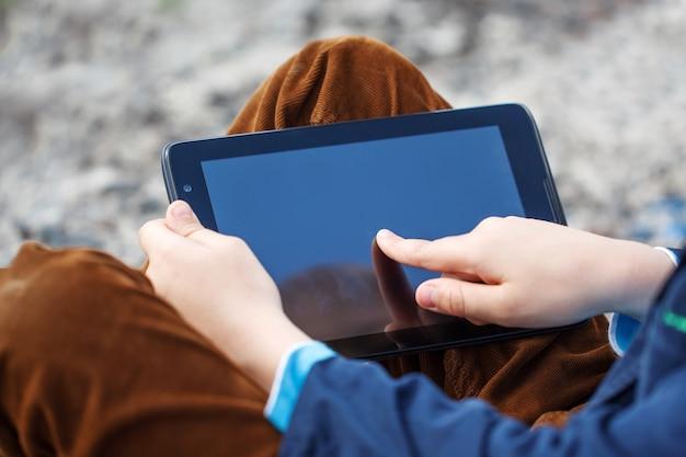 Sluit omhoog kleine jongen gebruikend tabletpc voor het spelen en onderwijs. Premium Foto