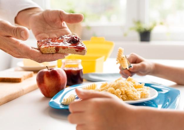 Sluit omhoog kleinkind en grootouder met voedsel