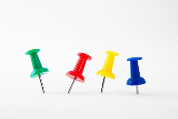 Sluit omhoog kleurrijke die punaise met groen, rood, geel en blauw op wit wordt geïsoleerd