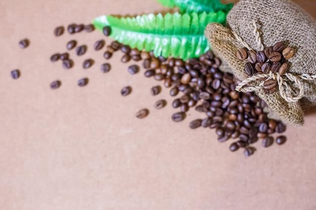 Sluit omhoog koffiebonen en de bonen van de onduidelijk beeldkoffie in de zak van de koffiejute op oude houten achtergrond.