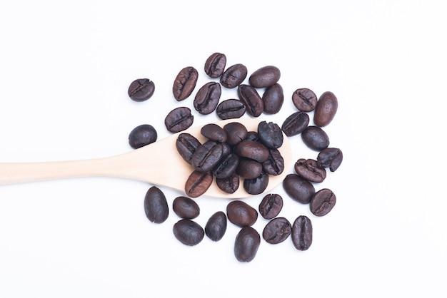Sluit omhoog koffiebonen in houten die lepel op wit wordt geïsoleerd