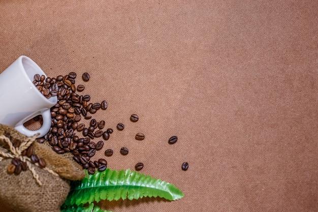 Sluit omhoog koffiebonen met de zak van de koffiejute en een witte kop op oude houten achtergrond.