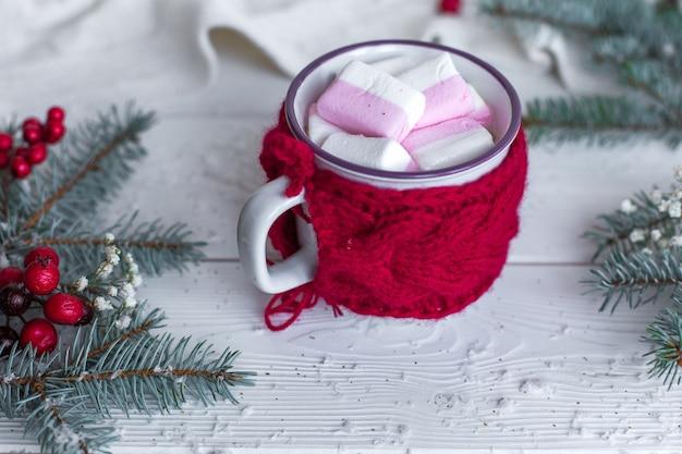 Sluit omhoog kop van hete chocolade met marshmellows op kerstmis verfraaide witte houten lijst