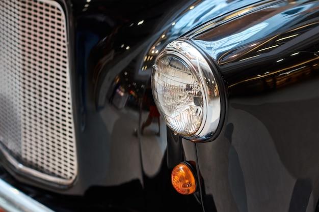 Sluit omhoog koplamp van een zwarte uitstekende auto
