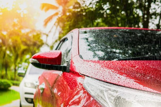Sluit omhoog koplamp van en regendaling op auto met regendruppelauto