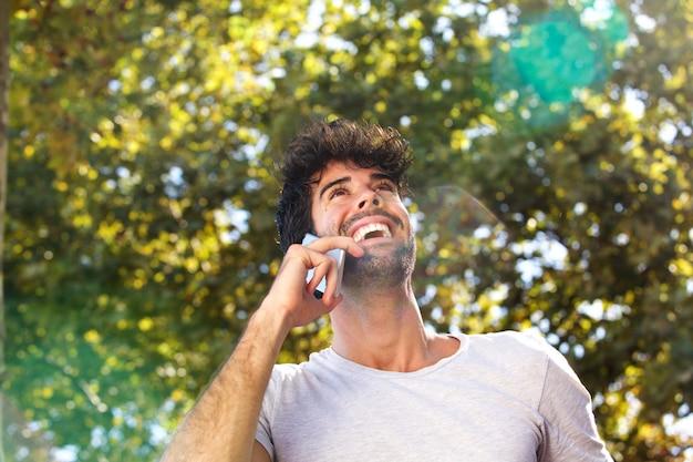 Sluit omhoog lachende mens die op mobiele telefoon buiten in de herfst spreken