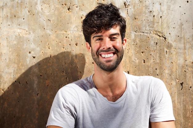 Sluit omhoog lachende mens met baardzitting door concrete muur