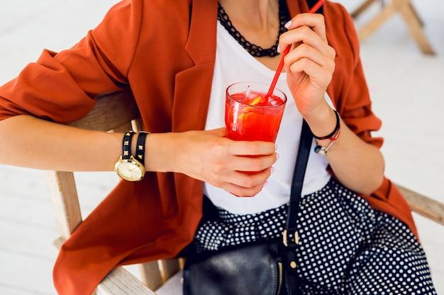 Sluit omhoog levensstijlportret van het leuke modieuze jonge vrouw openlucht stellen, zittend in de zomerkoffie en drinkend exotische cocktail, overzeese achtergrond. felle kleuren. vakantie stemming. glimlachen en plezier hebben.