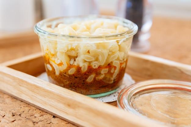 Sluit omhoog macaroni cheese baked met vleessaus in glaskom op houten dienblad.
