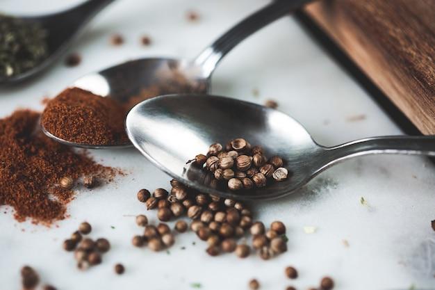 Sluit omhoog macrofoto van koriander. kruiden in verschillende lepels op stenen marmeren tafel. rustiek vintage kleurtoon