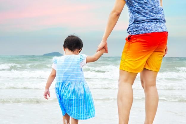 Sluit omhoog mamma hand in hand een kind op strand