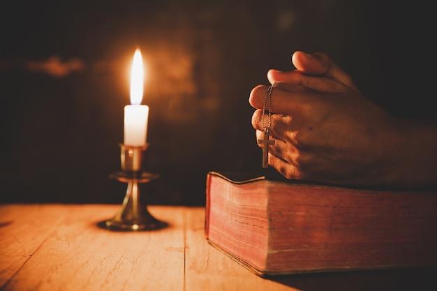 Sluit omhoog man hand bidt in de kerk met aangestoken kaars