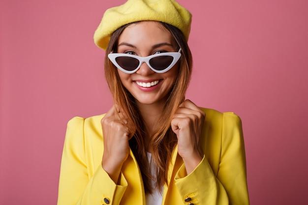 Sluit omhoog manierportret van leuke modieuze vrouw in geel kostuum en baret.