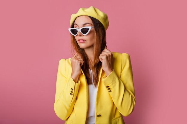 Sluit omhoog manierportret van modieuze vrouw in geel kostuum en baret.