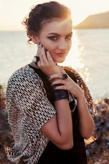 Sluit omhoog manierportret van mooie glimlachende vrouw bij zonneschijn. smokey eyes kijken.