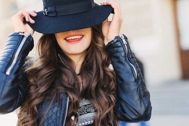 Sluit omhoog manierportret van vrij verleidelijke jonge vrouw met wolhoed glimlachen, lachen, openlucht stellen. rode lippen, golvend kapsel.