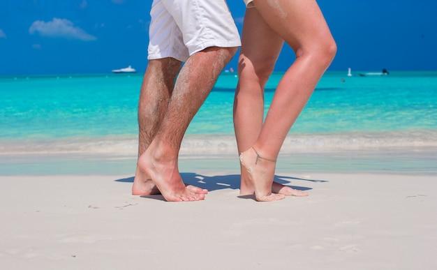 Sluit omhoog mannelijke en vrouwelijke voeten op wit zand