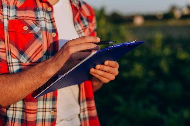 Sluit omhoog mannelijke handen die document documenten met pen houden en nota's schrijven