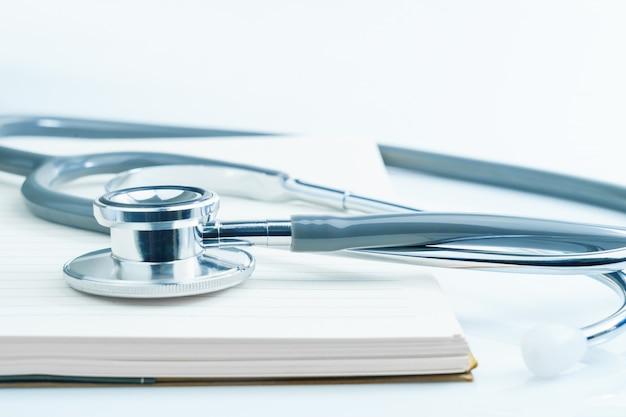 Sluit omhoog medische stethoscoop voor artsencontrole op de lijst van het gezondheids medische laboratorium met blocnote als medisch concept