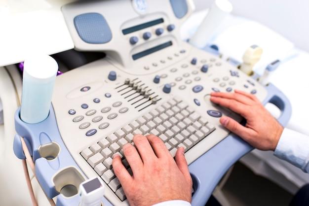 Sluit omhoog mening bij artsenhanden die aan ultrasone klankentoetsenbord werken