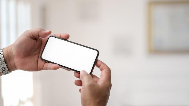 Sluit omhoog mening die van zakenman horizontale smartphone in eenvoudige bureauruimte houden