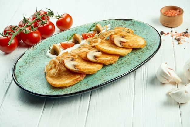 Sluit omhoog mening over aardappelpannekoeken met zure room en paddestoel op houten rustieke lijst. draniki