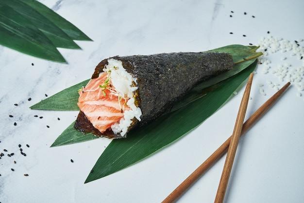 Sluit omhoog mening over de sushi van verse, temaki van zeevruchten met zalm op witte oppervlakte. traditionele handrol. horizontale, selectieve focus