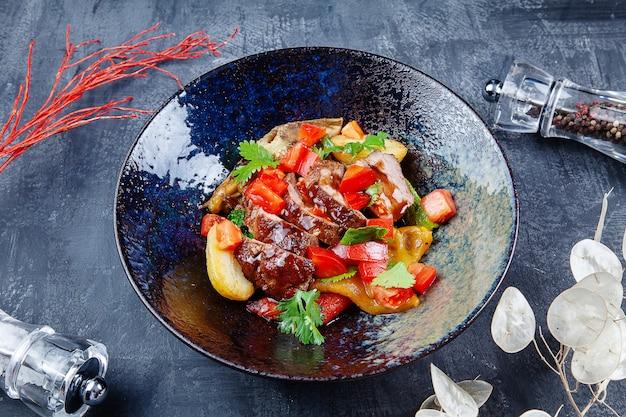 Sluit omhoog mening over gebakken groente en eendenborstsalade. lekkere, gezonde maaltijd voor een dieetmenu. saladeschaal. foodfoto voor menu of recept