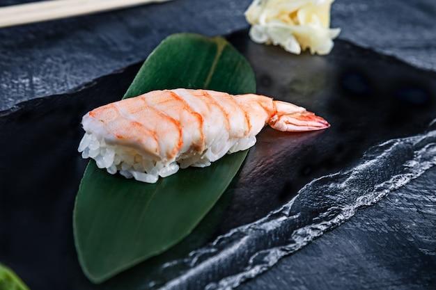Sluit omhoog mening over gediende nigiri met garnalen op donkere plaat op donkere oppervlakte