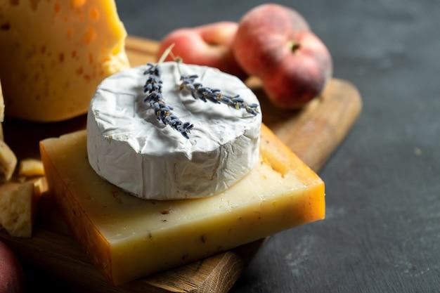 Sluit omhoog mening over kaas op donkere achtergrond. camembert, kaas met kruiden, hollandse kaas op snijplank met noten, lavendel en vijgen perzik. kopieer ruimte. plat gelegd voedsel. selectieve, zachte focus. donker humeurig