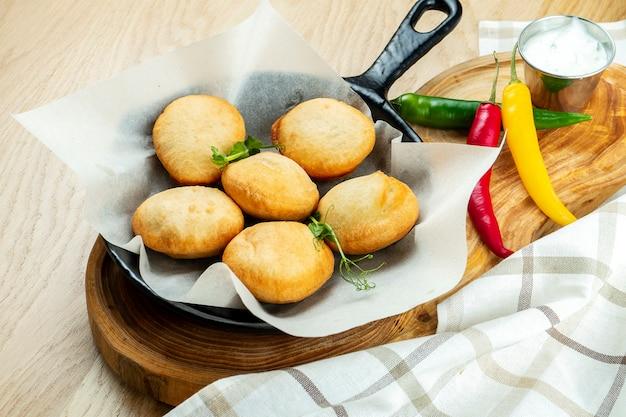 Sluit omhoog mening over panzerotto gevuld met vlees. kleine calzone gebakken op pan.