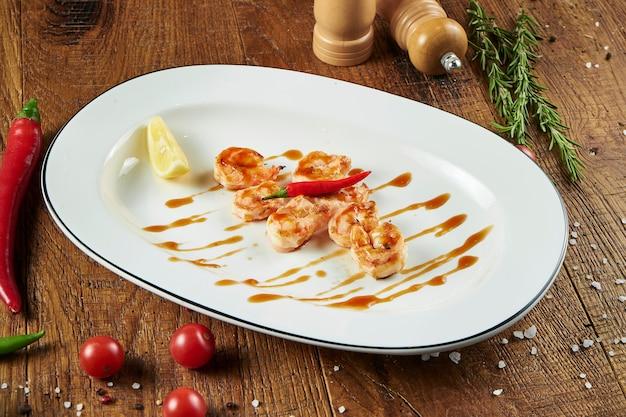 Sluit omhoog mening over sappige tijgergarnalen in zoetzure saus op een witte plaat op een houten oppervlakte in een samenstelling met kruiden. lekkere zeevruchten