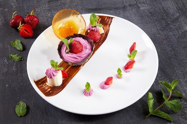 Sluit omhoog mening over smakelijk en koud aardbeiroomijs in een chocoladekom. vers dessert na de lunch. donkere achtergrond.