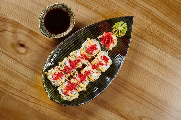Sluit omhoog mening over smakelijk gefrituurd sushibroodje met krab, tobikokaviaar op een zwarte plaat met sojasaus