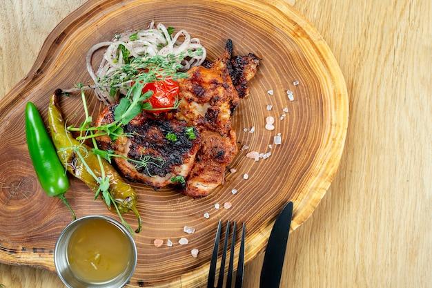 Sluit omhoog mening over smakelijk geroosterd lapje vlees van kip op houten raad. samenstelling met gekookt rundvlees, kruiden en groenten. fotowand voor eten. selectieve aandacht. sjasliek, kebab
