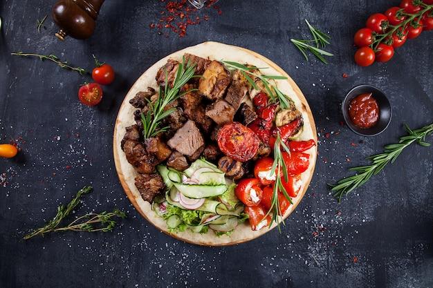 Sluit omhoog mening over smakelijk geroosterd vlees met groenten op georgisch pitabroodje. sjasliek of barbecuevlees op pita. shish kebab, traditionele georgische gerechten.
