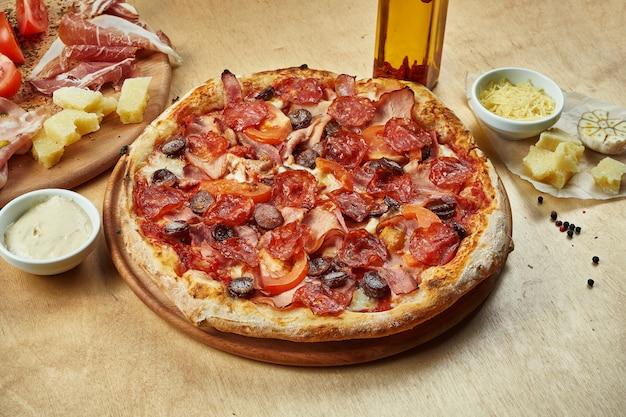 Sluit omhoog mening over smakelijke pizza met chorizosalami, ham, gerookte worsten, tomaten en rode saus op houten lijst in een restaurant. italiaanse keuken.