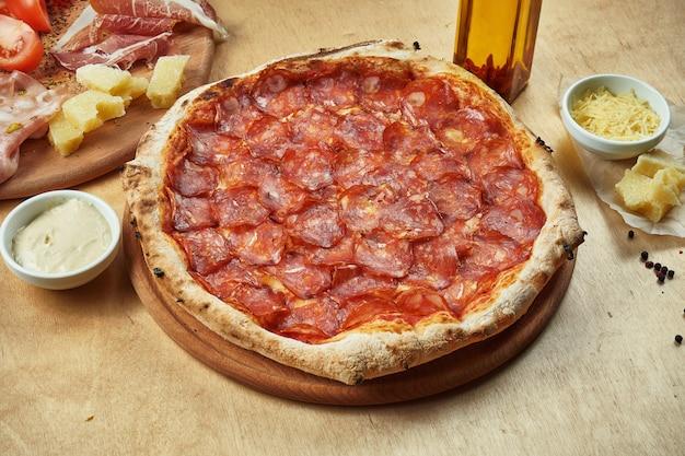Sluit omhoog mening over smakelijke pizza met pepperonisalami, rode saus en gesmolten kaas op houten lijst. italiaanse keuken.