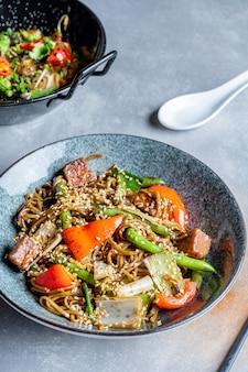 Sluit omhoog mening over sobanoedels met zoetzure saus, groenten in grijze kom