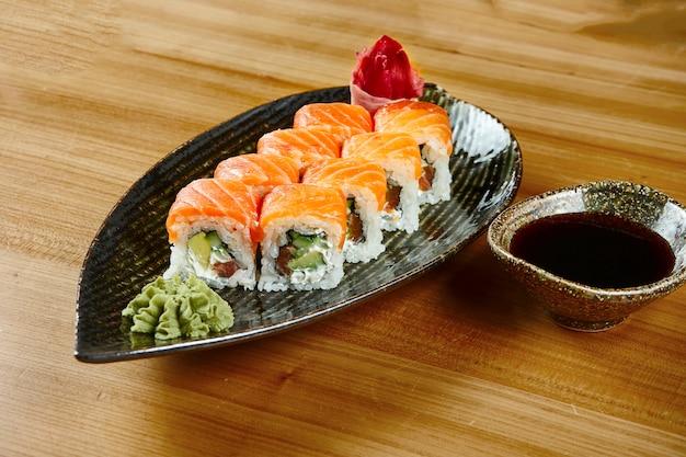 Sluit omhoog mening over sushibroodje met philadelphia met zalm, komkommer op een zwarte plaat met sojasaus