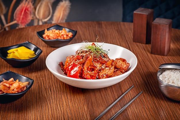 Sluit omhoog mening over traditioneel koreaans gesneden varkensvlees in zoetzure saus met slabladeren. vlees geserveerd met kimchi. koreaanse keuken met kopie ruimte. voedsel achtergrond.