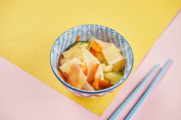 Sluit omhoog mening over traditionele kimchikool in blauwe kom op kleurrijke oppervlakte. pan-aziatische keuken