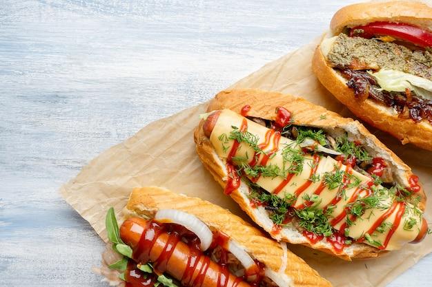 Sluit omhoog mening over verschillende voedsel gestileerde hotdogs met bovenste laagjes op lichte houten oppervlakte