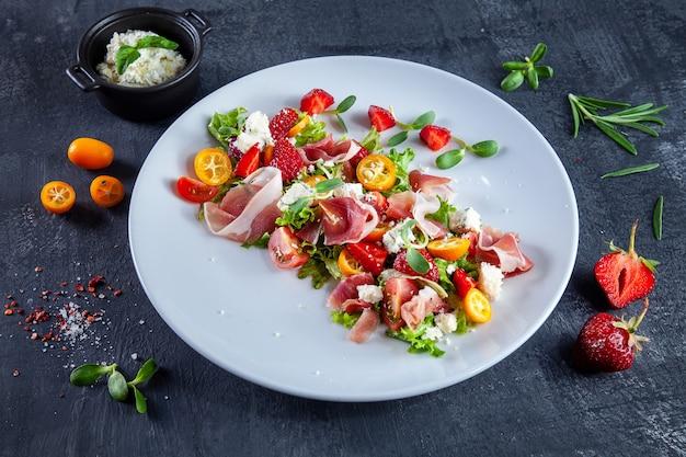 Sluit omhoog mening over verse, de zomersalade met kersentomaat, aardbei, jamon en microgreen. lekker eten plat. voedsel voor een gezonde en heerlijke lunch. kopieer ruimte.